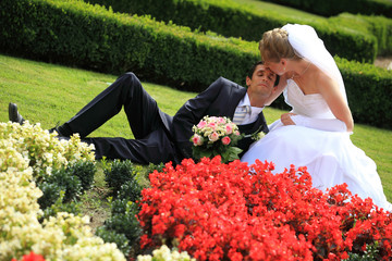 Young wedding couple lying in garden