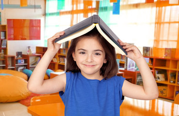 Brunette little girl with a book on her head