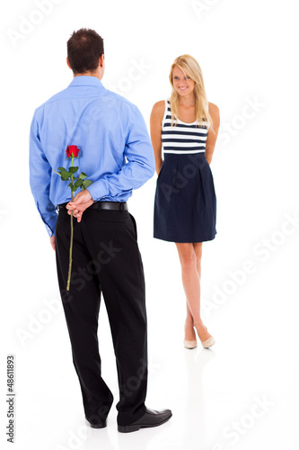 romantic young man hiding rose behind his back