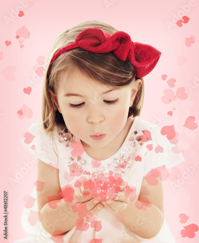Little girl blowing heart confetti on pink background
