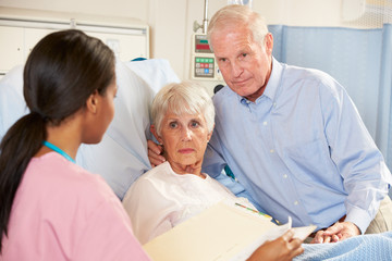 Nurse Talking To Senior Couple On Ward