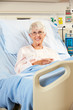 Portrait Of Senior Female Patient Relaxing In Hospital Bed