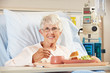 Senior Female Patient Eating Meal In Hospital Bed