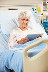Senior Patient Relaxing In Hospital Bed With Digital Tablet
