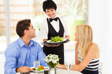 happy waitress serving customers in restaurant