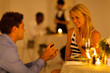 young man proposing to his girlfriend in a restaurant