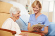 Nurse Taking Notes From Senior Female Patient Seated In Chair