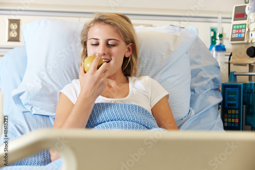 Teenage Female Patient Eating Apple In Hospital Bed