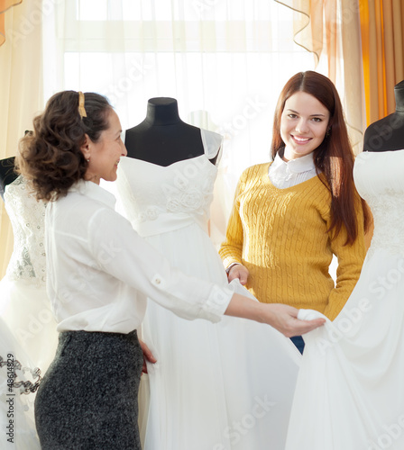 shop consultant helps girl chooses white bridal outfit