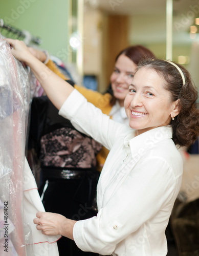 women chooses  dress at shop
