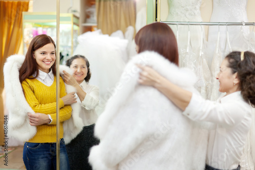 consultant helps bride chooses fur cape at shop