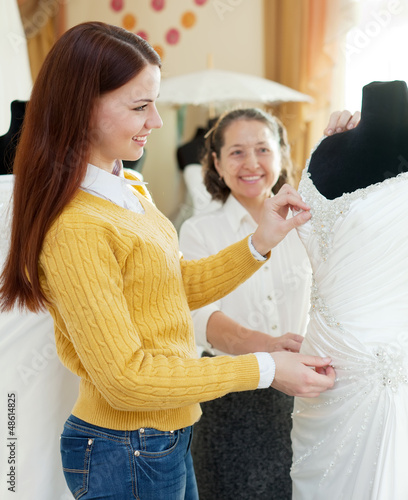 Happy mother  with daughter chooses bridal gown