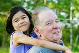Little girl hugging her grandfather outdoors, diversity