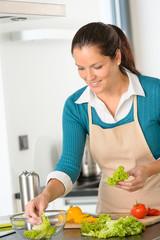 Smiling woman making salad vegetables kitchen preparing