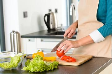 Cook woman cutting tomato salad knife kitchen