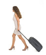 Young woman walking with wheels suitcase. Side view
