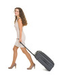 Happy young woman walking with wheels suitcase
