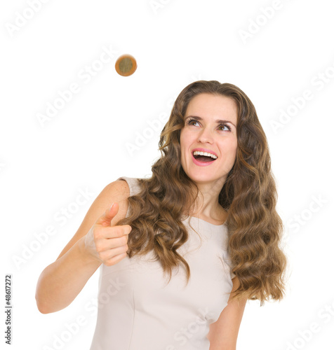 Happy young woman tossing coin
