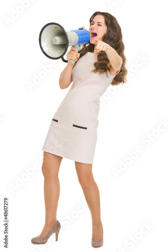 Full length portrait of young woman shouting in megaphone