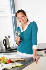 Smiling woman kitchen drinking wine preparing vegetables