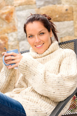 Smiling woman drinking hot cocoa relaxing garden