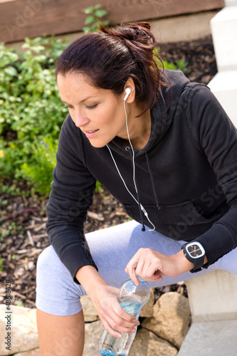 Tired woman relaxing running bottle headphones sweatsuit