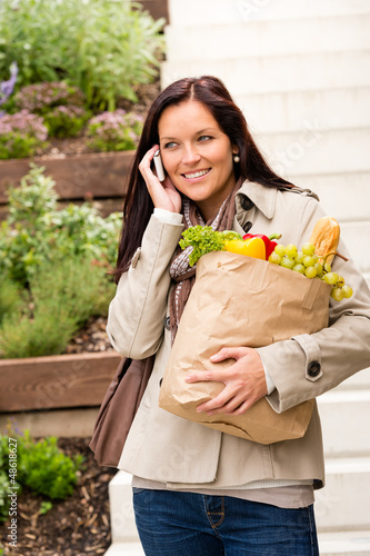 Happy woman shopping vegetables calling cell phone