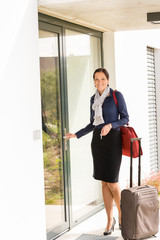 Smiling woman business flight attendant arriving home