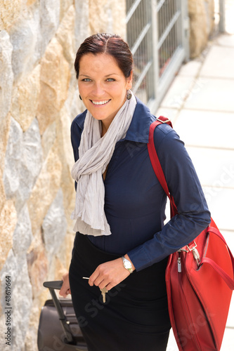 Happy businesswoman arriving home traveling luggage tired