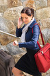 Happy woman calling hurried traveling luggage phone