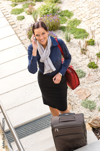 Pretty filght attendant leaving calling luggage phone