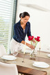 Young woman placing flowers dinner table