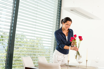 Smiling woman putting red roses dinner room