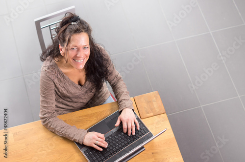 Frau sitzt lachend vor Notebook