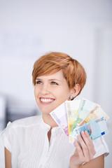 lächelnde frau hält geldscheine in der hand