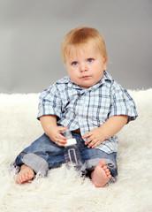 Little boy sitting on white carpet on gray background