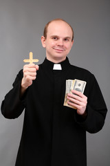 Young pastor with cross and money on gray background
