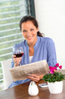 Cheerful woman reading drinking wine newspaper living