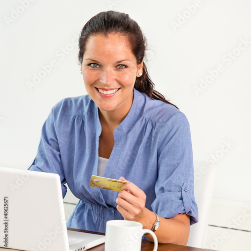 Smiling woman paying bills online banking home