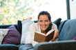 Smiling woman resting reading sofa learning domestic
