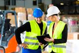 Forklift driver and supervisor at warehouse poster