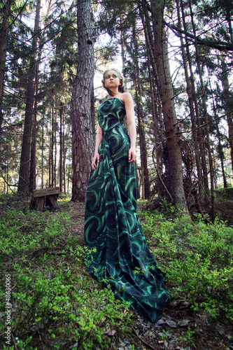 wild beauty blonde woman long green dress in the forest