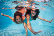 Mother and daughter having fun underwater in swimming pool.