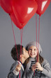 Young boy kissing girl with red heart balloons on grey