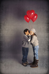 Small loving couple of kids with red heart balloons