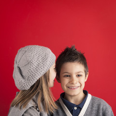 Couple of kids whispering on red background with copy space.