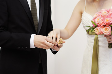 Bride holding ring during wedding ceremony