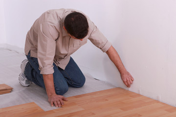 Man placing wooden floor