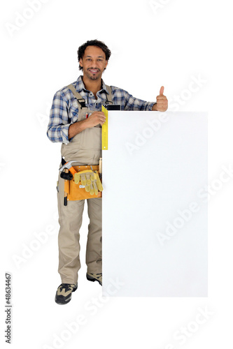 Tradesman using a try square to measure a board
