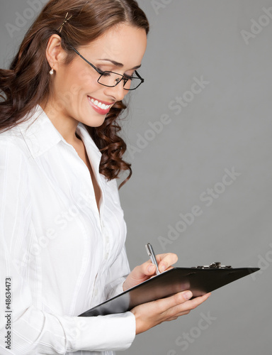 Businesswoman with clipboard writing, on gray